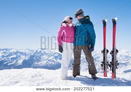 Skier couple standing on snowy mountain top and looking each other. Loving couple with skis with copy space. Couple enjoying ski winter holiday in snow mountain with beautiful landscape in background.