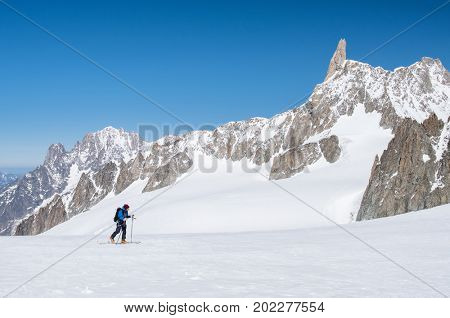 Mountaineer exploring a glacier with skis in winter expedition on Alps. Young alpine skier man climb on skis in a beautiful landscape covered by snow. Cross country skiing on Mont Blanc, Alps.