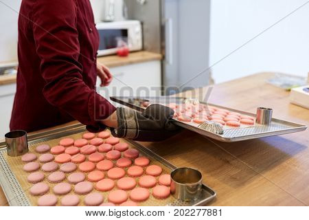 cooking, baking, confectionery and people concept - chef with macarons on oven tray at bakery kitchen