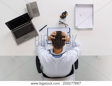 medicine, healthcare and people concept - doctor with cardiogram on clipboard and laptop computer holding to head at table in clinic