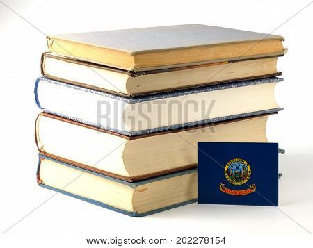 Idaho Flag With Pile Of Books Isolated On White Background