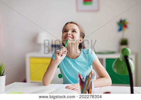 people, children, education and learning concept - happy girl with book and notebook looking up at home
