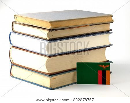 Zambia Flag With Pile Of Books Isolated On White Background