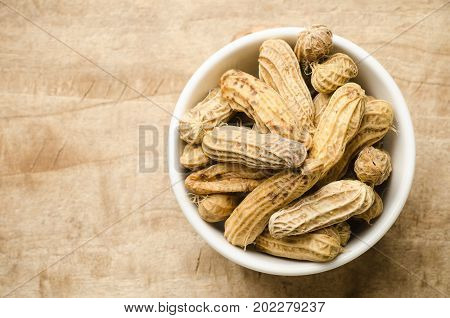 Boiled peanuts or groundnuts in a bowl on wooden background ready to eating