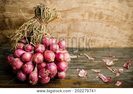 Raw shallots on wooden background, food ingredient