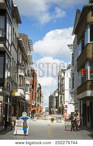 OOSTENDE BELGIUM - JUNE 22 2016: A street under construction with displays bulldozer and people in a sunny day with clouds. Oostende Belgium.