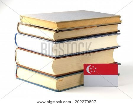 Singaporean Flag With Pile Of Books Isolated On White Background