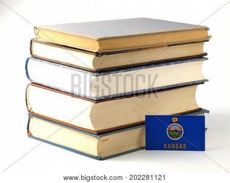 Kansas Flag With Pile Of Books Isolated On White Background
