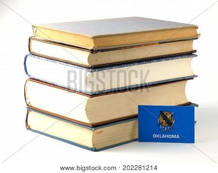 Oklahoma Flag With Pile Of Books Isolated On White Background