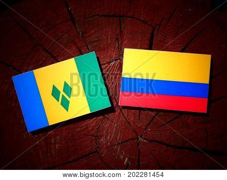 Saint Vincent And The Grenadines Flag With Colombian Flag On A Tree Stump Isolated