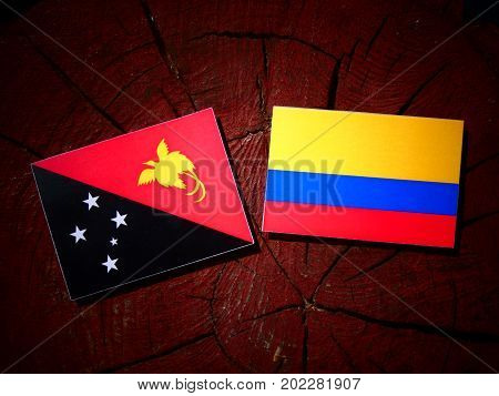 Papua New Guinea Flag With Colombian Flag On A Tree Stump Isolated
