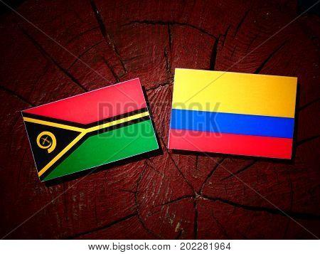 Vanuatu Flag With Colombian Flag On A Tree Stump Isolated