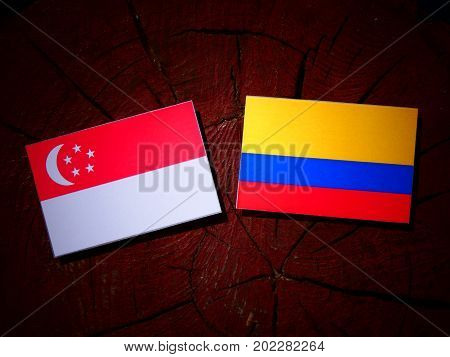 Singaporean Flag With Colombian Flag On A Tree Stump Isolated