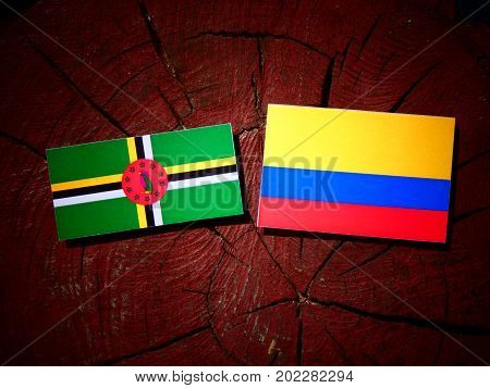 Dominica Flag With Colombian Flag On A Tree Stump Isolated