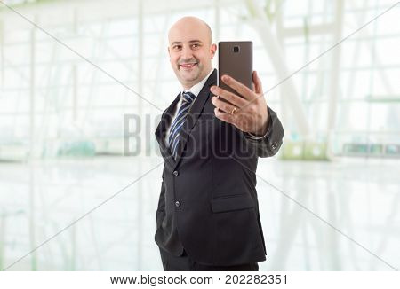 businessman in suit and tie taking selfie photo with mobile phone camera posing happy and successful at the office