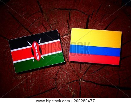 Kenyan Flag With Colombian Flag On A Tree Stump Isolated