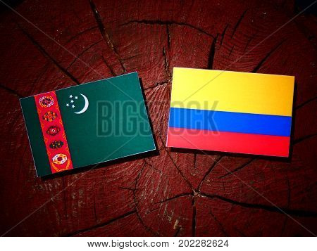 Turkmenistan Flag With Colombian Flag On A Tree Stump Isolated