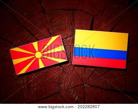 Macedonian Flag With Colombian Flag On A Tree Stump Isolated