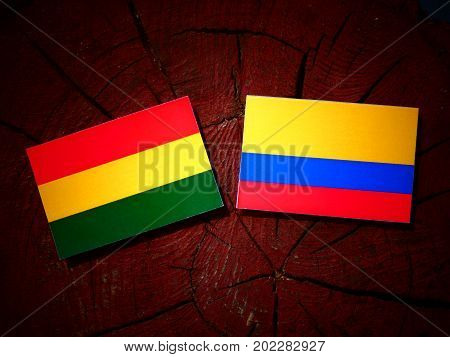 Bolivian Flag With Colombian Flag On A Tree Stump Isolated