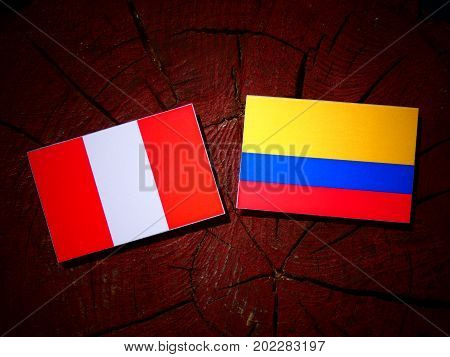Peruvian Flag With Colombian Flag On A Tree Stump Isolated