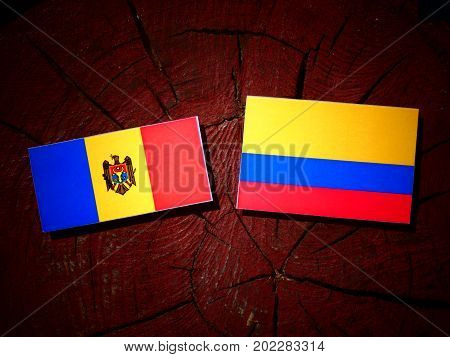 Moldovan Flag With Colombian Flag On A Tree Stump Isolated