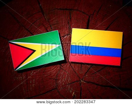 Guyana Flag With Colombian Flag On A Tree Stump Isolated