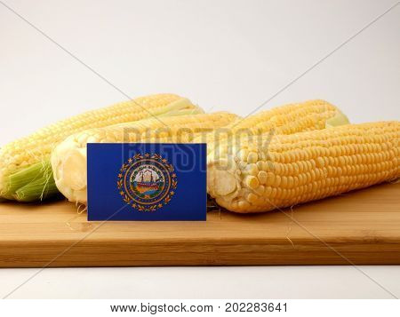 New Hampshire Flag On A Wooden Panel With Corn Isolated On A White Background