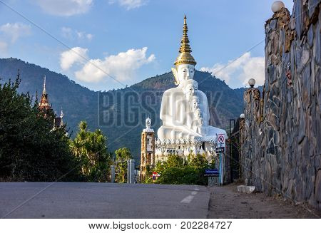 Road to white buddha statue and mountain background with blue sky in afternoon time.