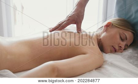 Blonde woman is given a massage for shoulder. Tibetan Medicine