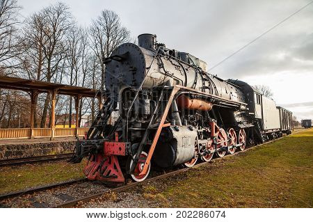 Old vintage steam locomotive from XX century, black and red color. Russian empire and USSR