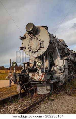 Old vintage steam locomotive from XX century, grey color. Russian empire and USSR