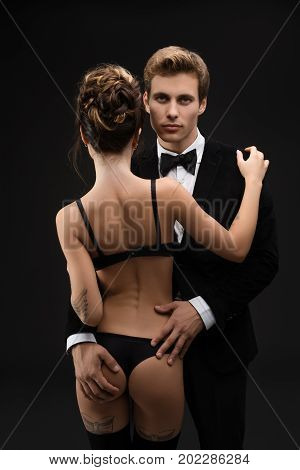 Handsome young gentleman wearing suit and bow tie embracing his sexy tattoed girlfriend in black lingerie and silk stockings staying in rearview isolated on black