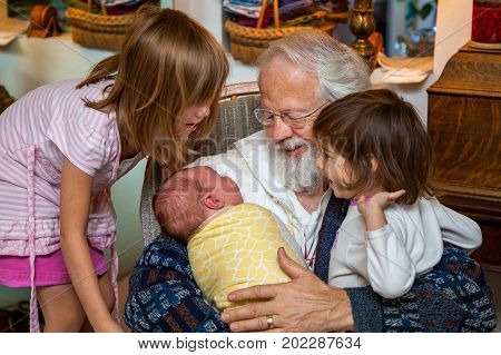 Grandpa holds his brand new grandson as he and two older sisters of the baby look at the boy in complete adoration.