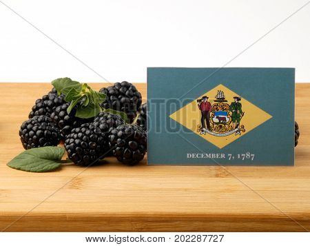 Delaware Flag On A Wooden Panel With Blackberries Isolated On A White Background