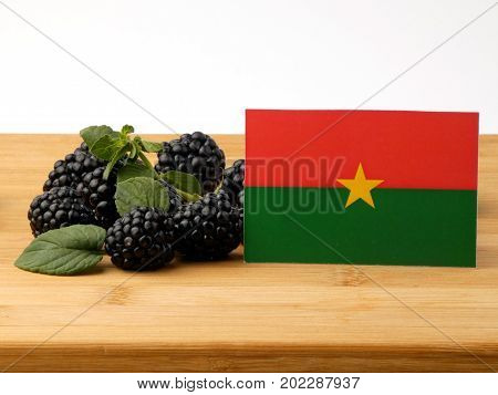 Burkina Faso Flag On A Wooden Panel With Blackberries Isolated On A White Background