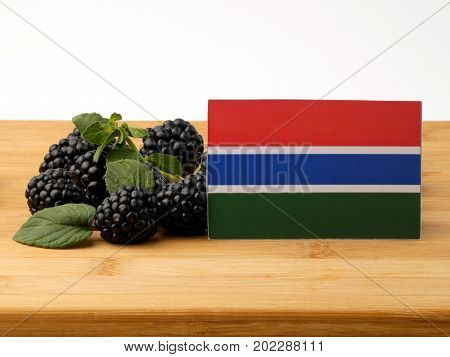 Gambia Flag On A Wooden Panel With Blackberries Isolated On A White Background