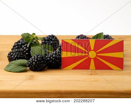 Macedonian Flag On A Wooden Panel With Blackberries Isolated On A White Background