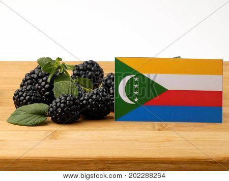 Comoros Flag On A Wooden Panel With Blackberries Isolated On A White Background