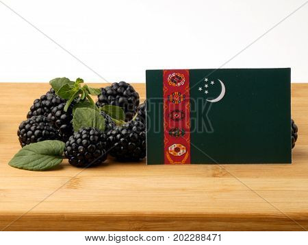 Turkmenistan Flag On A Wooden Panel With Blackberries Isolated On A White Background