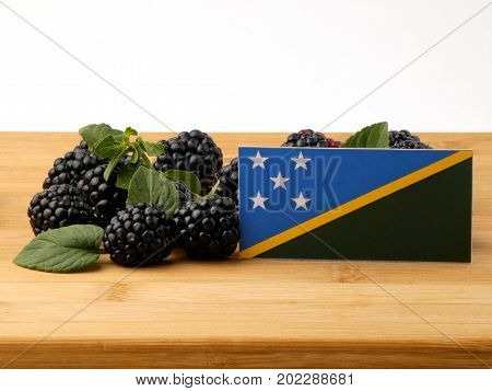 Solomon Islands Flag On A Wooden Panel With Blackberries Isolated On A White Background