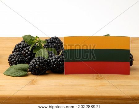 Lithuanian Flag On A Wooden Panel With Blackberries Isolated On A White Background