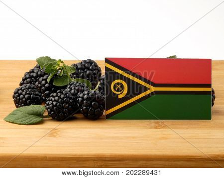 Vanuatu Flag On A Wooden Panel With Blackberries Isolated On A White Background