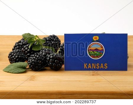 Kansas Flag On A Wooden Panel With Blackberries Isolated On A White Background