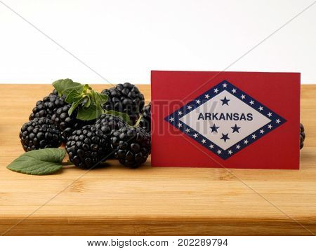 Arkansas Flag On A Wooden Panel With Blackberries Isolated On A White Background