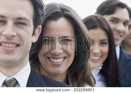 Hispanic co-workers standing in row