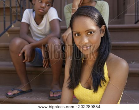 Close up of African woman with family in background