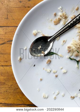 Empty dish with spoon and fork after eating on the wooden table. Top view of empty plate dirty after the meal is finished