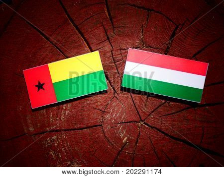Guinea Bissau Flag With Hungarian Flag On A Tree Stump Isolated