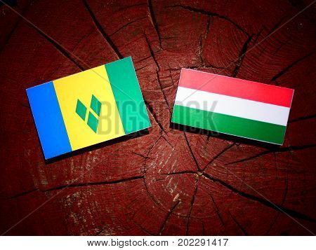 Saint Vincent And The Grenadines Flag With Hungarian Flag On A Tree Stump Isolated