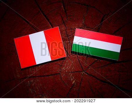 Peruvian Flag With Hungarian Flag On A Tree Stump Isolated